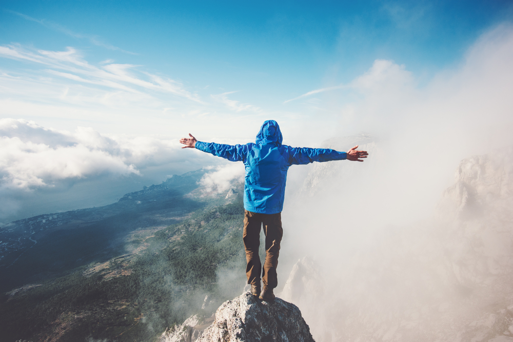 a man standing on the summit of a mountain with outstretched arms