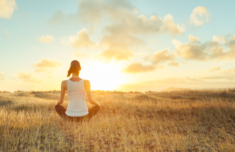 a woman practicing mindfulness meditation in a field
