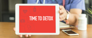 doctor holding tablet that says detox