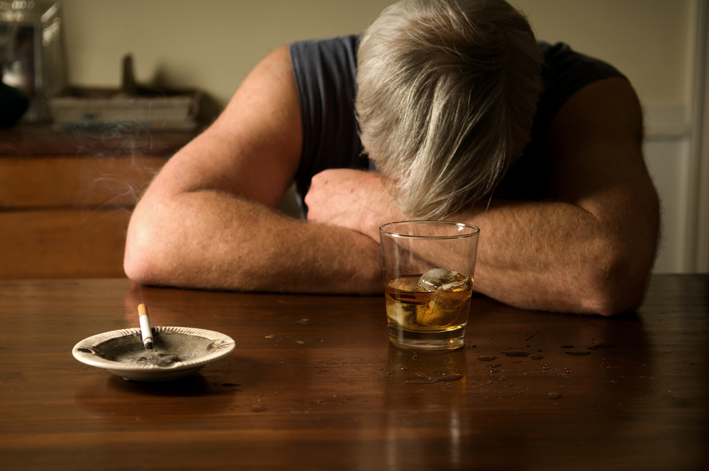 man with head down alcohol
