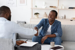 Motivational Interviewing addiction counselor shaking hands with client