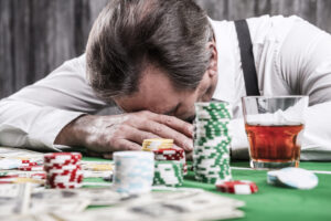 old man slumped at poker table with drink